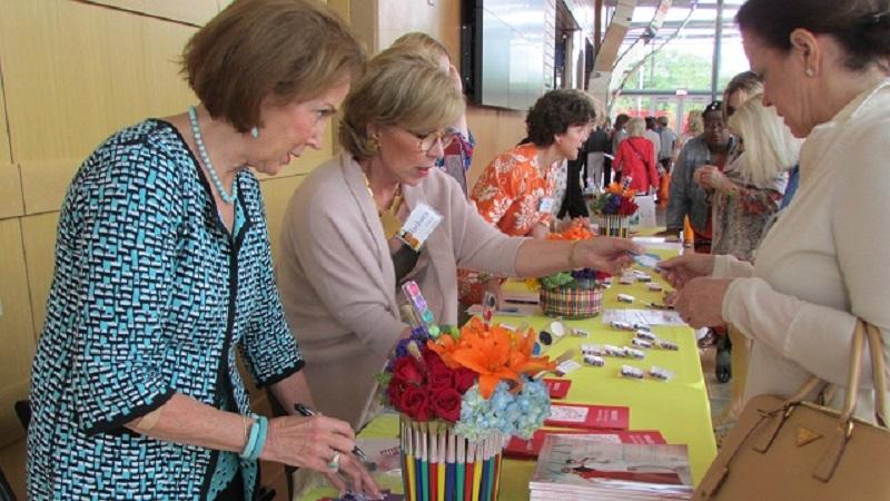 Women help participants check into an event