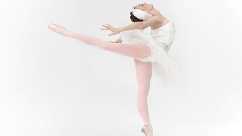 Ballerina dressed in white tutu performs
