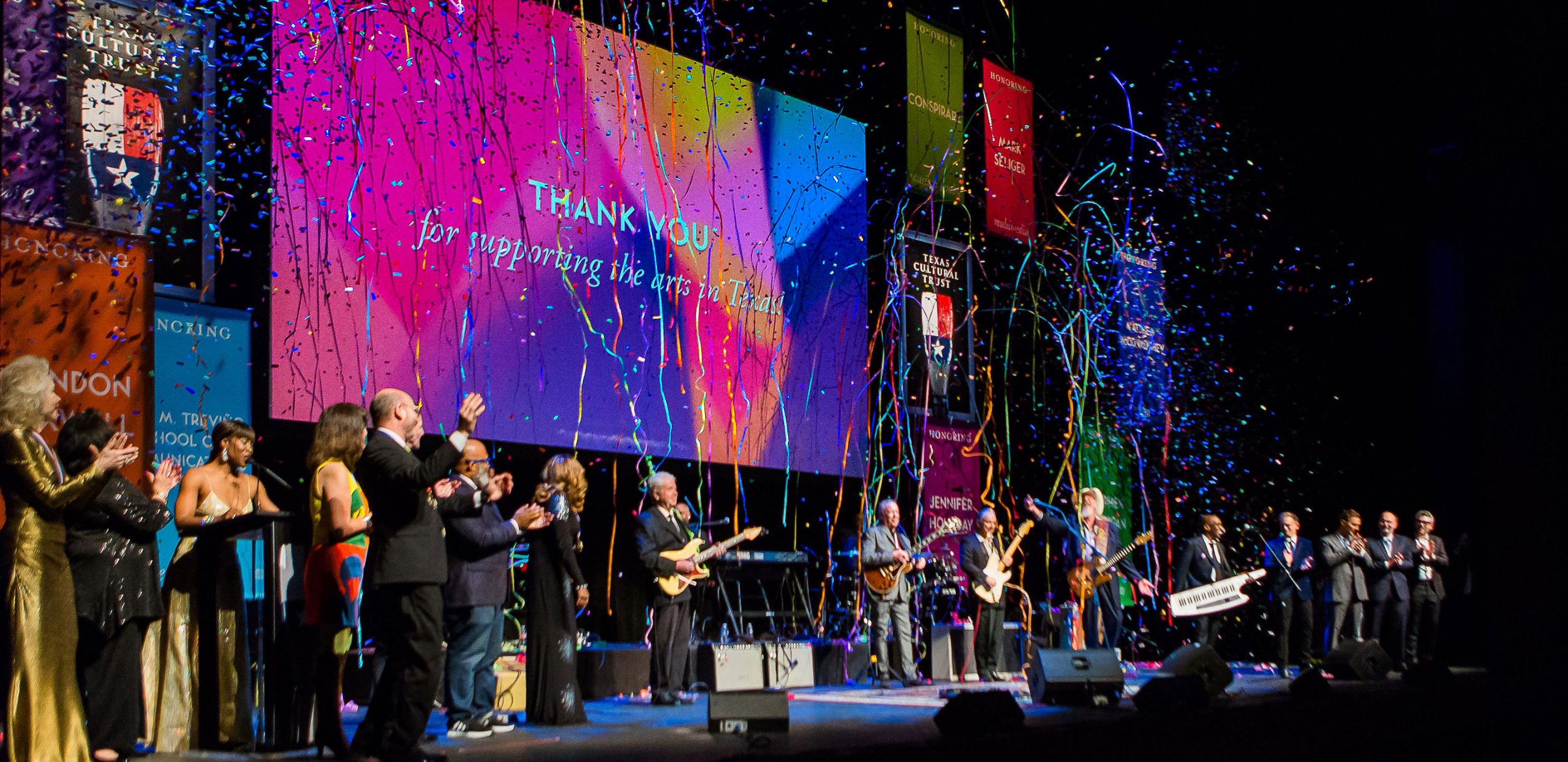Confetti falls on a stage of honorees in thanks of supporting the arts in Texas