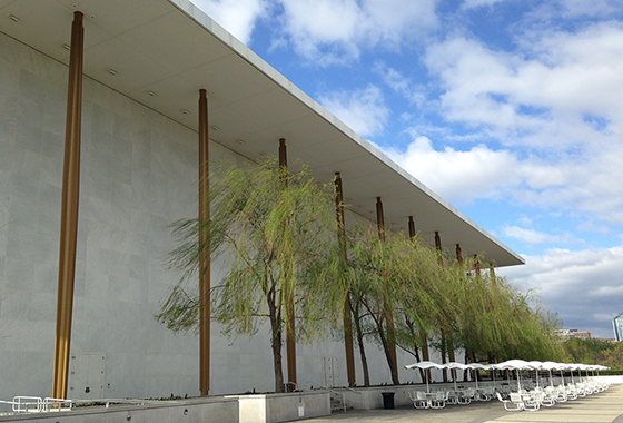 exterior shot of the Kennedy Center with trees and blue skies