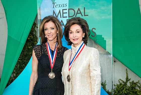 2015 co-chairs wearing medals in front of TMAA signage at event